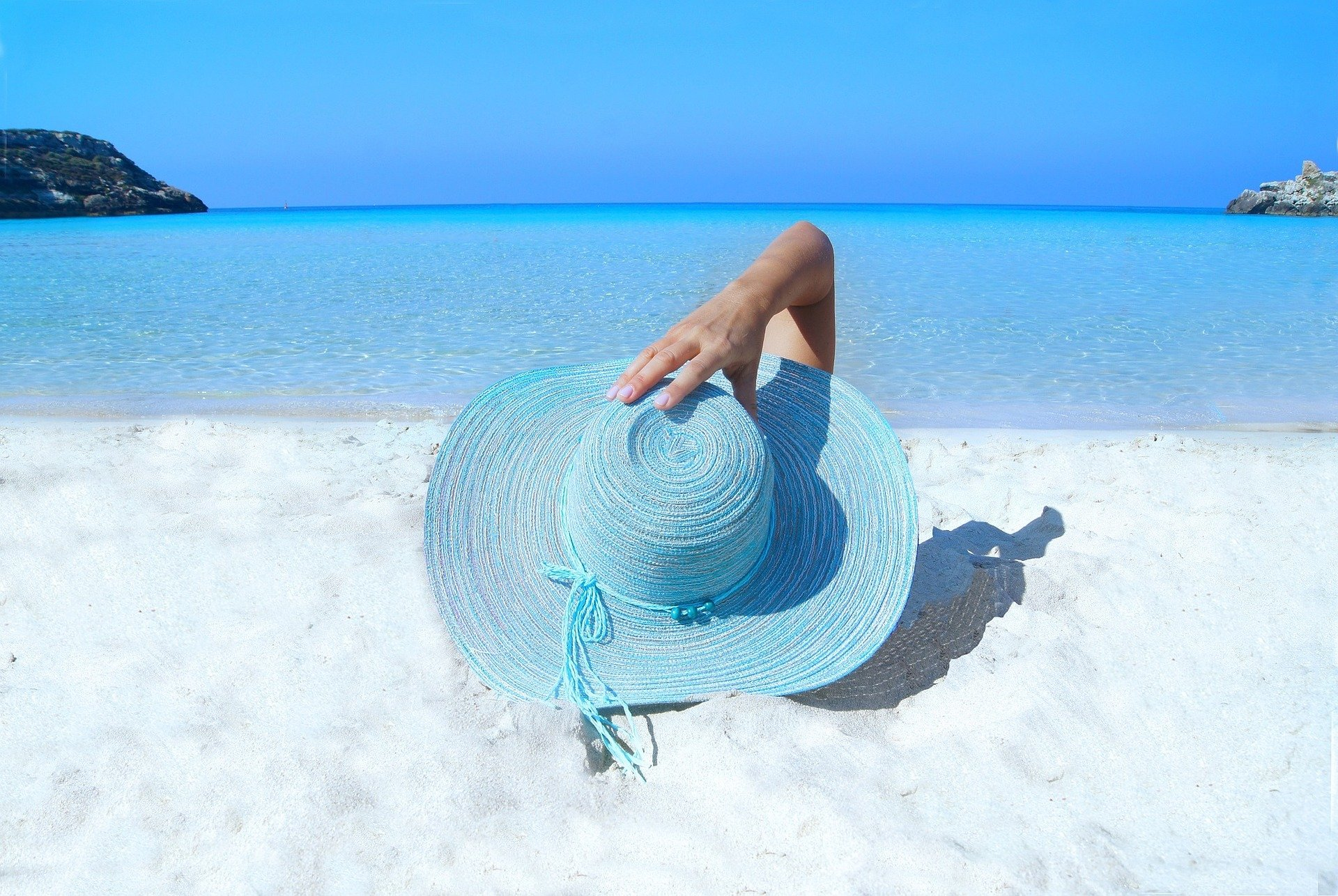 image of lady lying on beach with hat