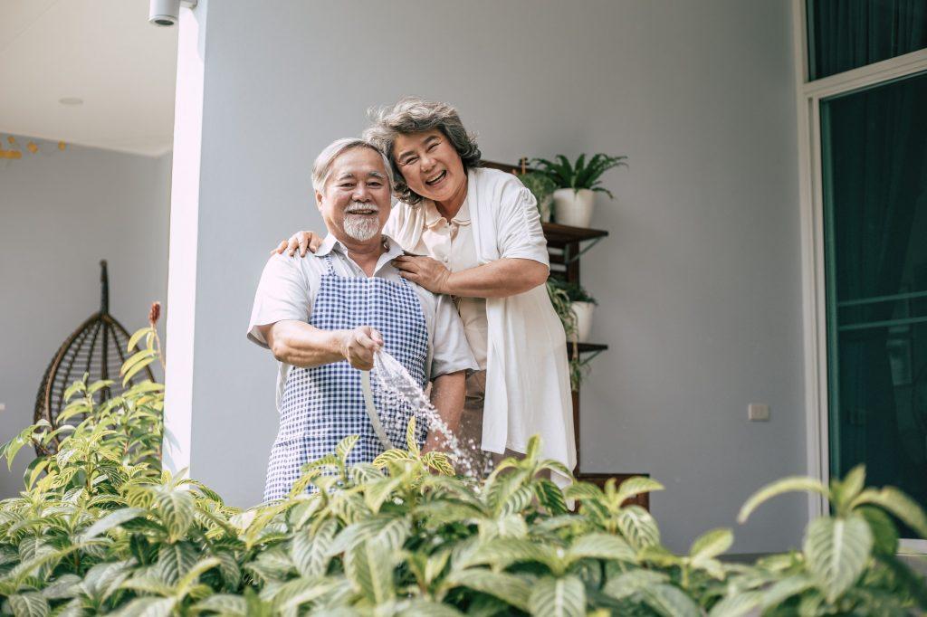 elderly couple watering a flower in home garden 1024x682 1